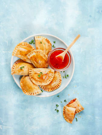Tuna patty with tomato and pepper, typical Spanish empanadas with sauce on light surface, copy space.