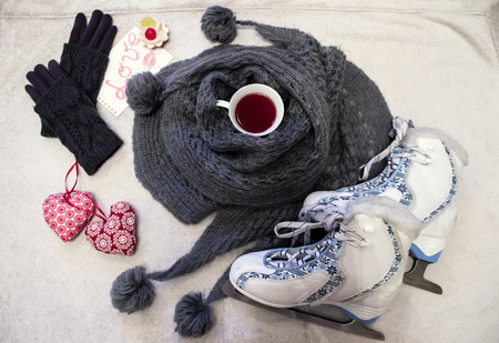 White-blue figure skates, warm gray skarf with pompons, cup of tea, knitted gloves and cute textile hearts Stock Photo
