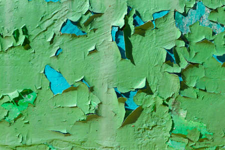 The photo of cracked and peeling paint on the old wall. Grunge texture - Abstract background. Scratched and chipped surface
