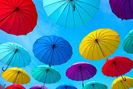 Bright multicolored umbrellas in the sky. Sun and rain protection on the street. 免版税图像