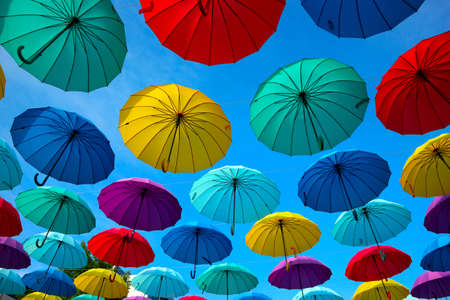 Colorful umbrellas in the sky. Sun and rain protection on the street. 免版税图像