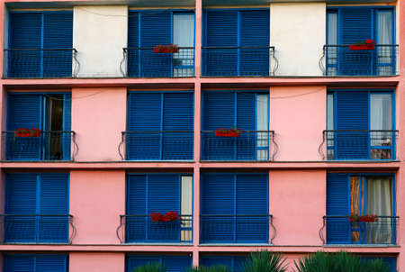 Balconies, flower decorations and windows with closed and open blue shutters in an apartment building.
