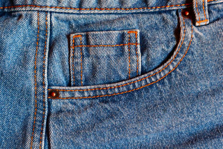 Blue jeans watch pocket close up, denim textile texture for wear advertising and fashion blogs.