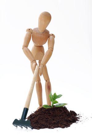 marioneta de madera: Cultivo de una planta, una nueva idea de concepto. Puppy con equipos de jardiner�a
