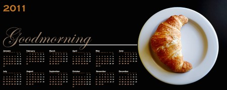2011 calendar with a croissant in a dish on black background with copy space photo