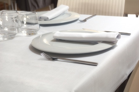 restaurant table for six with dishes, glasses, napkins and silverware Standard-Bild