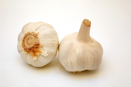 flavouring: Two bulbes of fresh white garlic cloves used for their pungent flavour as a seasoning and flavouring in cooking on a white studio background