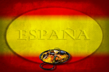 Traditional spanish dish: paella valenciana on spanish flag photo