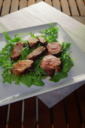 Sliced pork tenderloin with rocket on white dish photo
