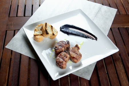 Sliced pork tenderloin with brown sauce on white dish photo