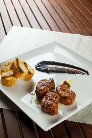 rocket lettuce: Sliced pork tenderloin with brown sauce on white dish Stock Photo