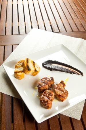 Sliced pork tenderloin with brown sauce on white dish photo