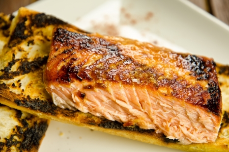 Roasted salmon on a white plate, wooden table on background