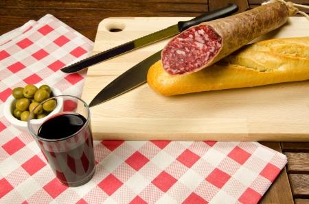 Apéritif intime avec salami, pain, olives et vin rouge Banque d'images - 16601356