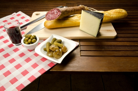 antipasti: Homelike appetizer with salami, bread, olives, cheese, pickles and red wine