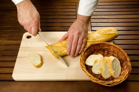 slicing: Chefs hands detail while slicing bread on wooden cutting board