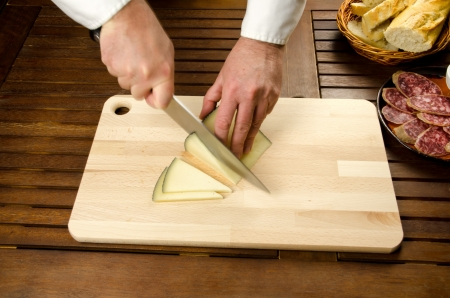 slicing: Chefs hands detail while slicing cheese on wooden cutting board Stock Photo