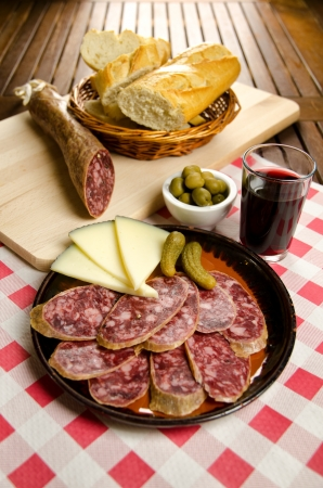 Homelike appetizer with salami, bread, olives, cheese, pickles and red wine photo