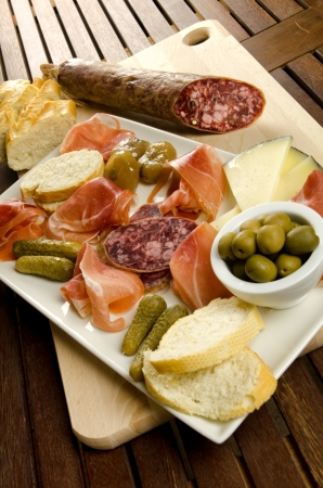 antipasti: Homelike appetizer with salami, bread, olives, cheese, ham, pickles and red wine