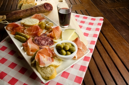 homelike: Homelike appetizer with salami, bread, olives, cheese, ham, pickles and red wine