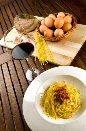 Spaghetti alla carbonara, traditional recipe with pasta, egg and bacon photo