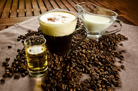 Warm Irish Coffee with coffee beans, whiskey and cream