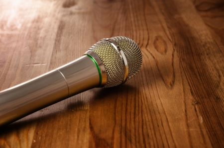 Wireless microphone for karaoke, wooden background with copyspace photo