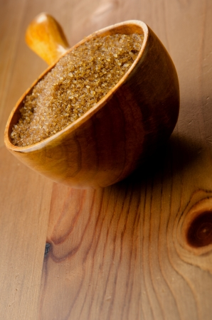 Brown cane sugar in a wooden spoon on wood background photo