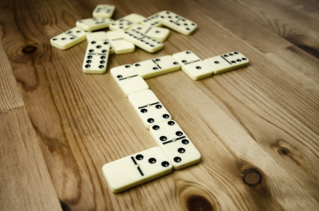dominoes: Close up of dominowith black dots on wooden background