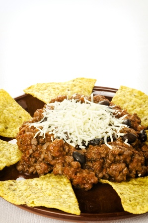 Mexican food: cheesy chili with meat served with nachos photo