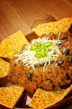 Mexican food: chili with meat served with nachos on wooden background photo