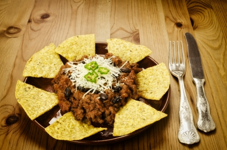 Mexican food  chili with meat served with nachos on wooden background photo
