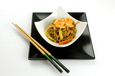 chinese noodles: Delicious Chinese noodles topped with shrimps served in a stylish contemporary white porcelain bowl on a square black plate with chopsticks for healthy seafood cuisine, studio shot on white Stock Photo