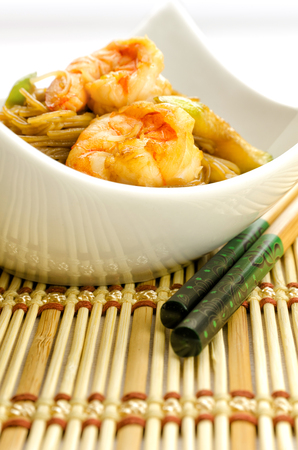 chinese noodles: Delicious Chinese noodles topped with shrimps served in a stylish contemporary white porcelain bowl with chopsticks for healthy seafood cuisine, studio shot on white
