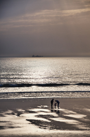 love life: Family silhouette on the beach, mother, father and daughter Stock Photo