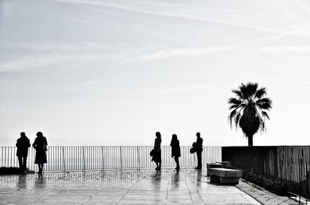 mujer mirando el horizonte: la gente relajada disfrutando de la vista desde la terraza por encima de la orilla del mar en Lisboa, Portugal. Silueta de un disparo con copyspace.