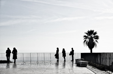 viewpoints: Relaxed people enjoying the view from terrace above the seaside in Lisbon, Portugal. Silhouette shot with copyspace. Stock Photo