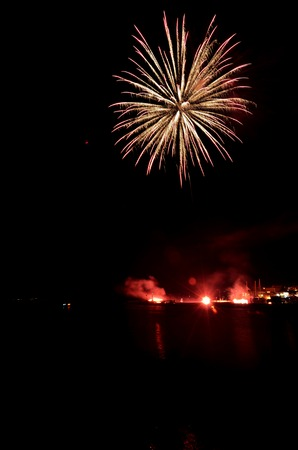 Nightscene with multicolor fireworks on the sea, summer celebration at the seaside resort
