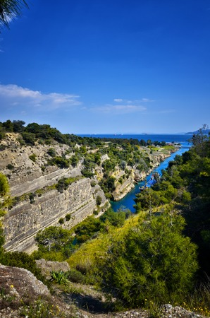 The Corinth Canal connects the Gulf of Corinth with the Saronic Gulf in the Aegean Sea in Greece. It cuts through the narrow Isthmus of Corinth and separates the Peloponnese from the Greek mainland