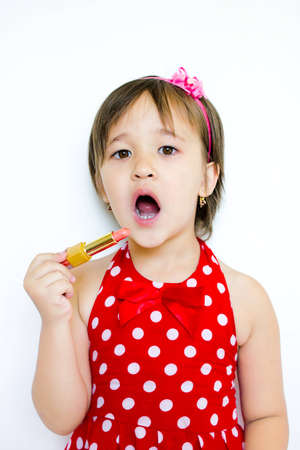 little girl paints her lips with lipstick Stock Photo - 14184637