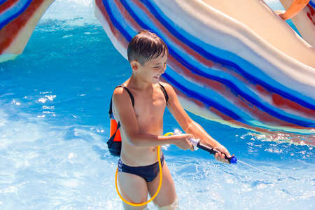 a little boy playing in the pool with a water pistol