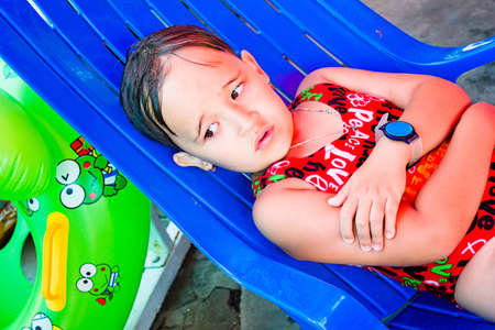 lounger: little girl lies on a lounger by the pool Stock Photo