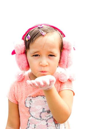 a little girl in a pink dress sends a kiss