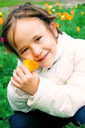innocent little girl with a yellow flower in the hands