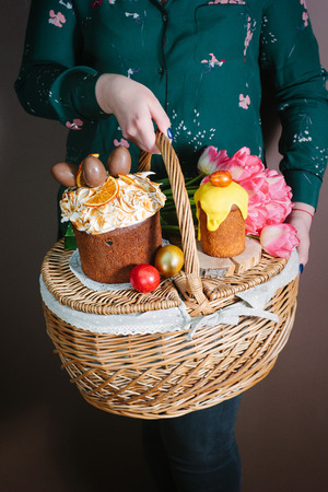 Woman holding a basket with Easter eggs and Easter cakes