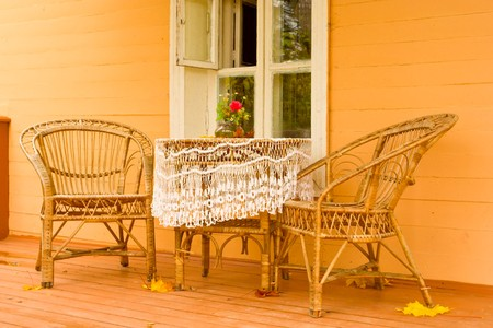 Cozy veranda with wicker garden furniture in a traditional Russian village house. photo