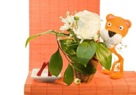 Hand made orange knitted tiger for ornamental pattern and vase with white rose  photo