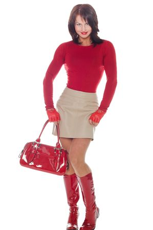 young woman poses in a short leather skirt and red lacquer boots photo