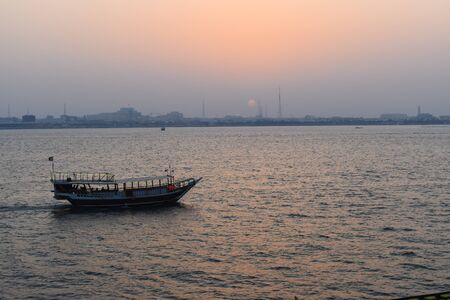 Beautiful tranquil scene of a dhow boat on the calm sea in Doha, Qatar, at sunset.