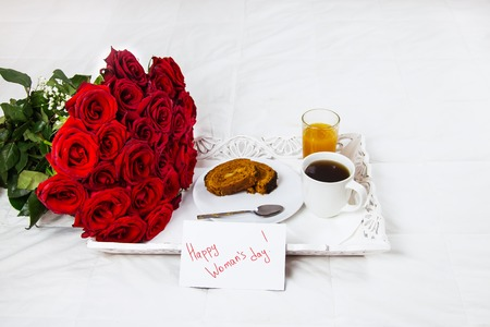 Breakfast in bed, celebrate valentines day, womens day or birthday. White bed, large bouquet of red roses. In the background of a pillow, a bedside table unfocus. copy space, free space. Stock Photo